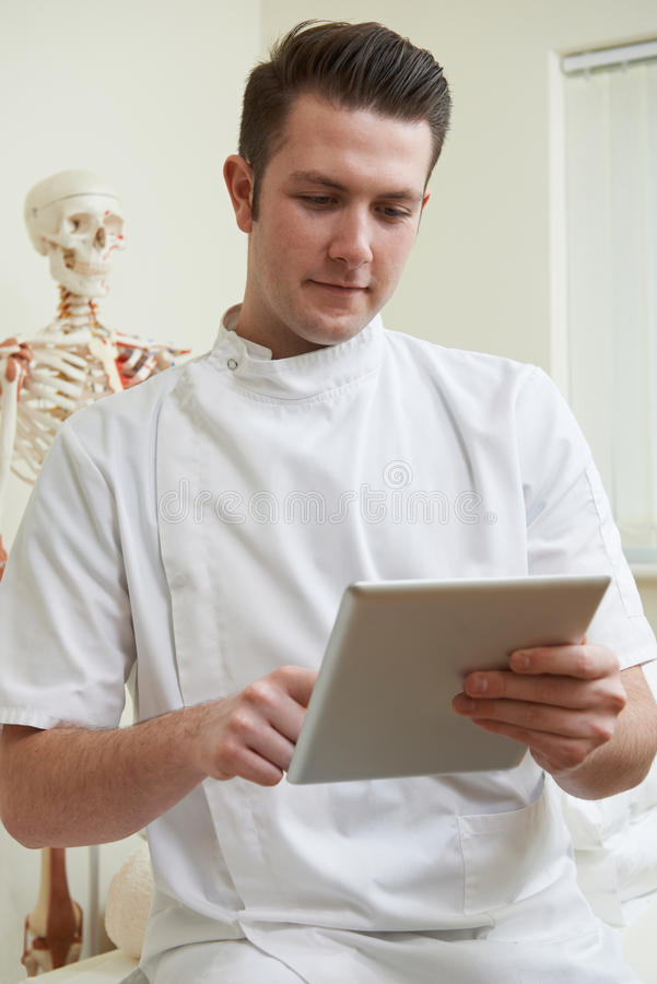Ostéopathe masculin dans la chambre de consultation utilisant la Tablette de Digital image libre de droits