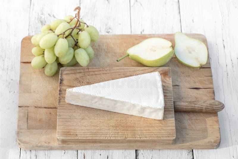 Ost, druvor och päron för brie för ostplatta mjuk på den vita tabellen arkivbilder