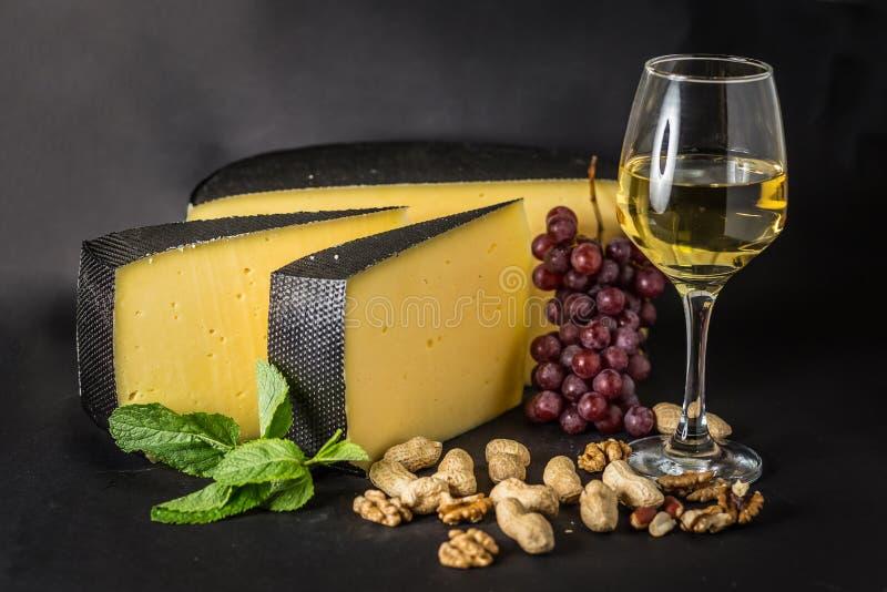 Ost med druvan, vitt vin, jordnötter och mintkaramellen royaltyfri fotografi