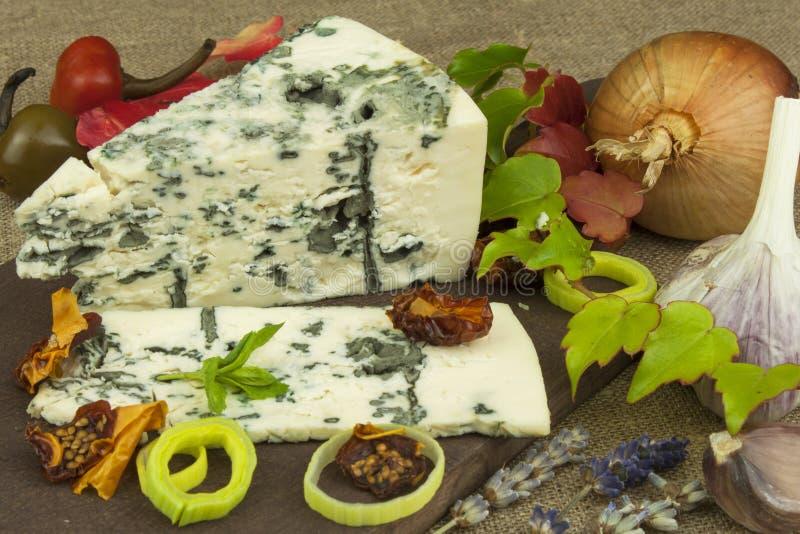 Ost med formen på en träskärbräda Förberedelse av aromatisk ost Stiltonost på träostbräde arkivbild