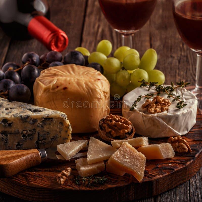 Ost, muttrar, druvor och rött vin på träbakgrund royaltyfri fotografi