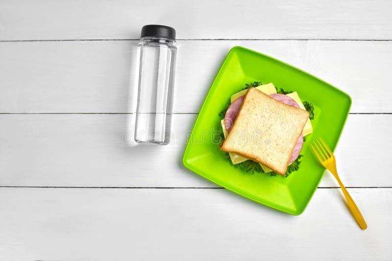 Ost och skinksmörgås, flaska av vatten på den vita trätabellen Sunt lunchidébegrepp royaltyfria bilder