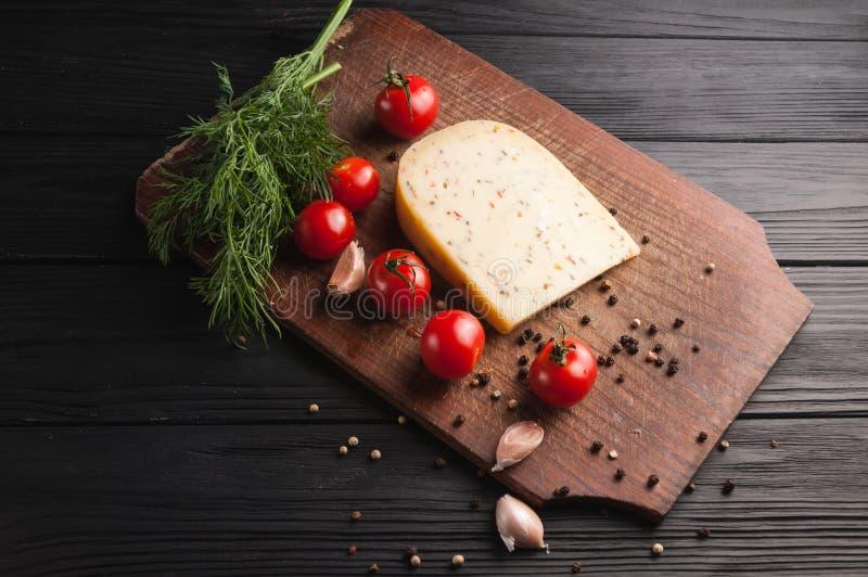 Ost på ett brunt träbräde på en svart träbakgrund, körsbärsröda tomater, peppar, gräsplaner, kryddor, dill, persilja arkivfoton