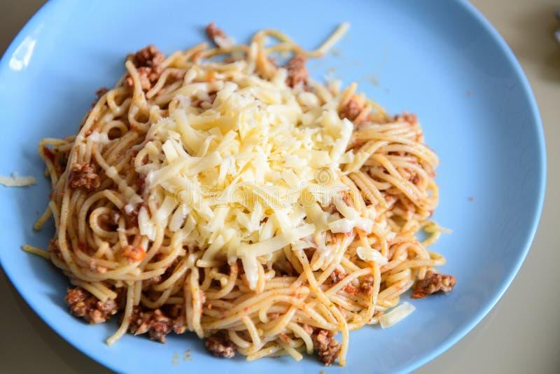 Ost på pasta med kött, pasta på en blå platta royaltyfri foto
