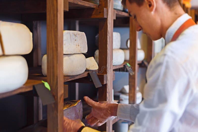 Ost shoppar assistenten som väljer någon ost royaltyfri bild