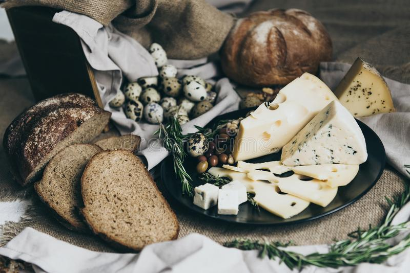 Ostar som ligger på svart maträtt och bröd, placerade närliggande Ädelost ost med hål dekorerade med örter Stort stycke av arkivfoton
