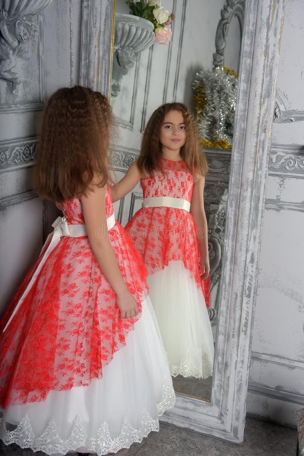 Ostart das Mädchen der Brunette im Weiß mit einem roten eleganten Kleid lizenzfreies stockfoto