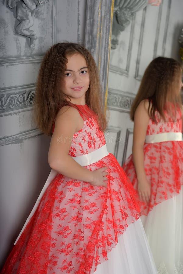 Ostart das M?dchen der Brunette im Wei? mit einem roten eleganten Kleid stockfotos