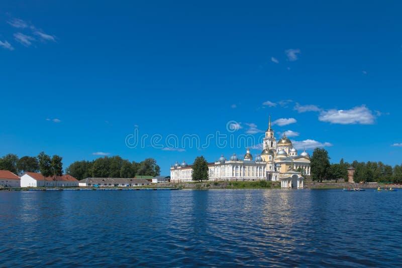 OSTASHKOV, SELIGER, ROSJA: Nilov monaster na Seliger jeziorze Żółty budynku Niebieskie niebo i błękitny jezioro w lecie zdjęcia royalty free