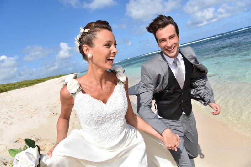Ostatnio zamężni potomstwa dobierają się bieg na plaży zdjęcia royalty free