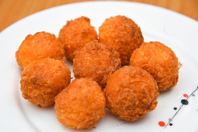 Ostbollar, bröad mozzarellaost klumpa ihop sig med tomaten i den vita maträtten på träblackground arkivbilder