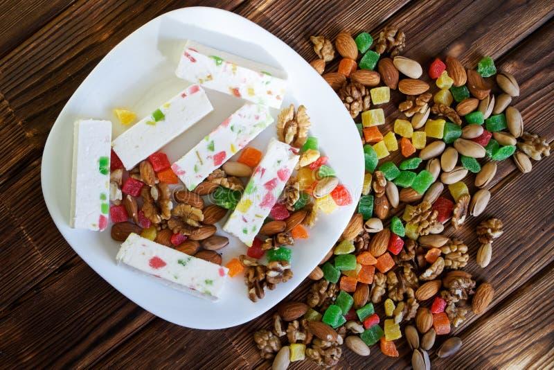 Ostbonbons: weiße Pastille nahe bei kandierter Frucht, Pistazien, Mandeln und Walnüssen Nationale arabische Teller stockfotografie
