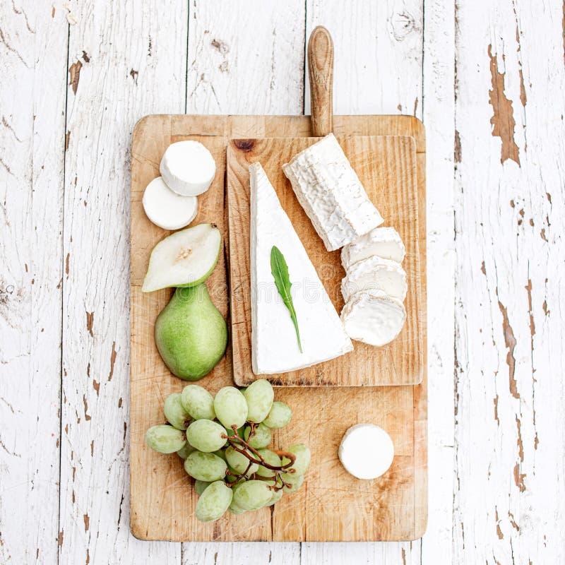 Ostbräde med det olika ost, päronet och druvor på vit träbakgrund B?sta sikt f?r ostuppl?ggningsfat kopiera avst?nd royaltyfria bilder