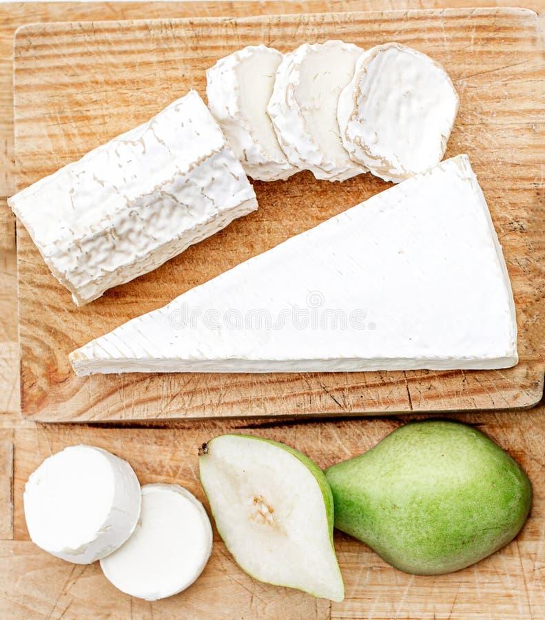Ostbräde med det olika ost, päronet och druvor på vit träbakgrund B?sta sikt f?r ostuppl?ggningsfat kopiera avst?nd fotografering för bildbyråer
