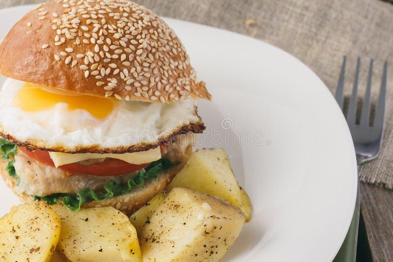 Ostburgare med stekte ägg- och potatisvedges arkivfoton