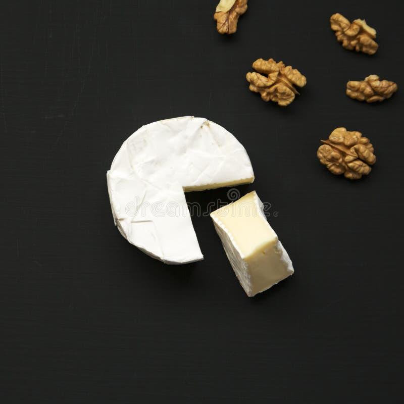 Ostcamembert eller brie med valnötter på svart bakgrund Mjölka produktion Top beskådar Lekmanna- lägenhet royaltyfri foto