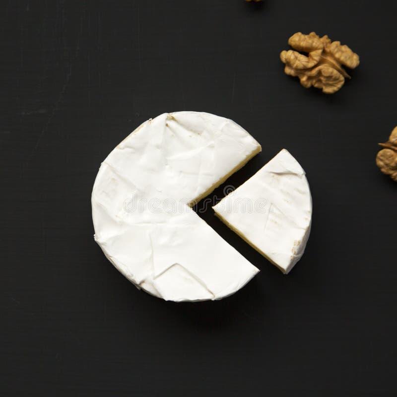 Ostcamembert eller brie med valnötter på svart bakgrund, uppe i luften Mjölka produktion Top beskådar Lekmanna- lägenhet royaltyfria bilder