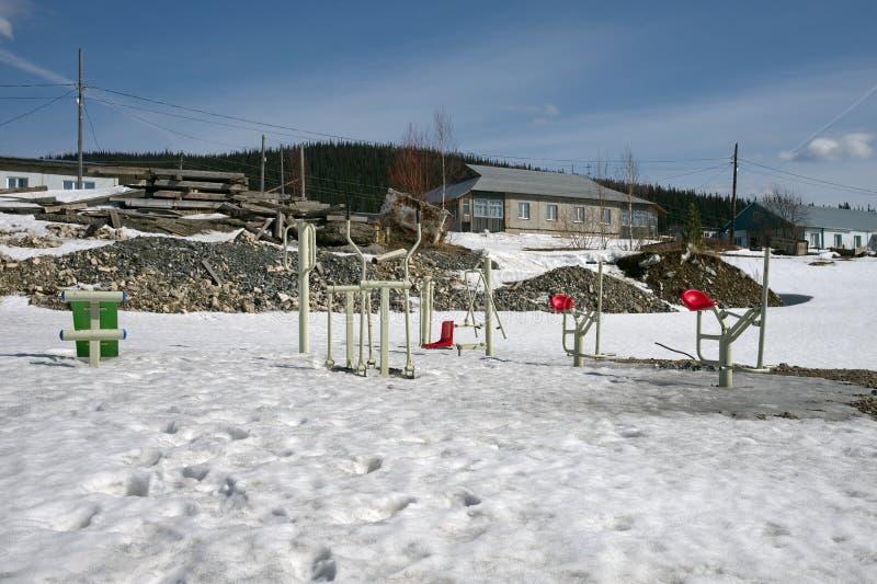 Ostenta a aproximação amigável dos simuladores para fora de debaixo da neve em uma rua da vila na primavera fotografia de stock