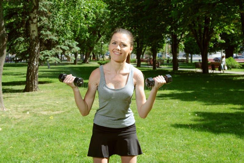 Ostenta a menina que faz o exercício com pesos claros fotografia de stock royalty free