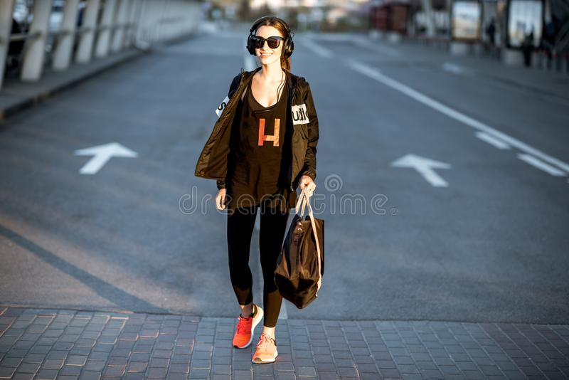Ostenta a mulher que anda na rua após o treinamento fotografia de stock