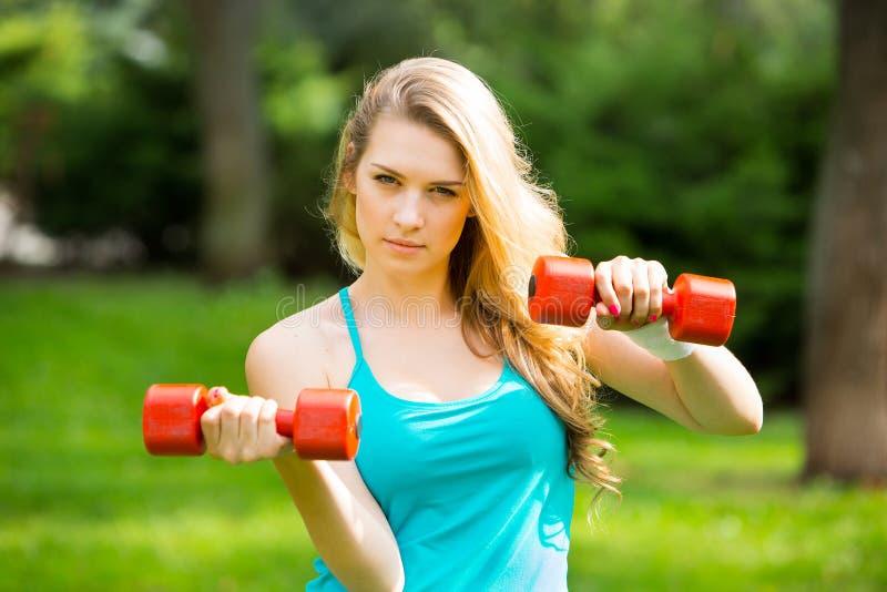 Ostenta o exercício da menina com pesos no parque fotografia de stock