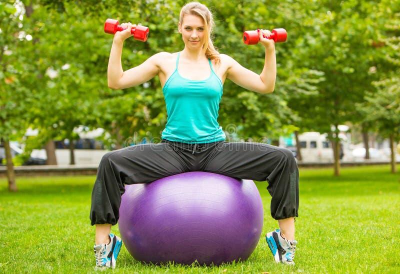 Ostenta o exercício da menina com pesos no parque imagem de stock
