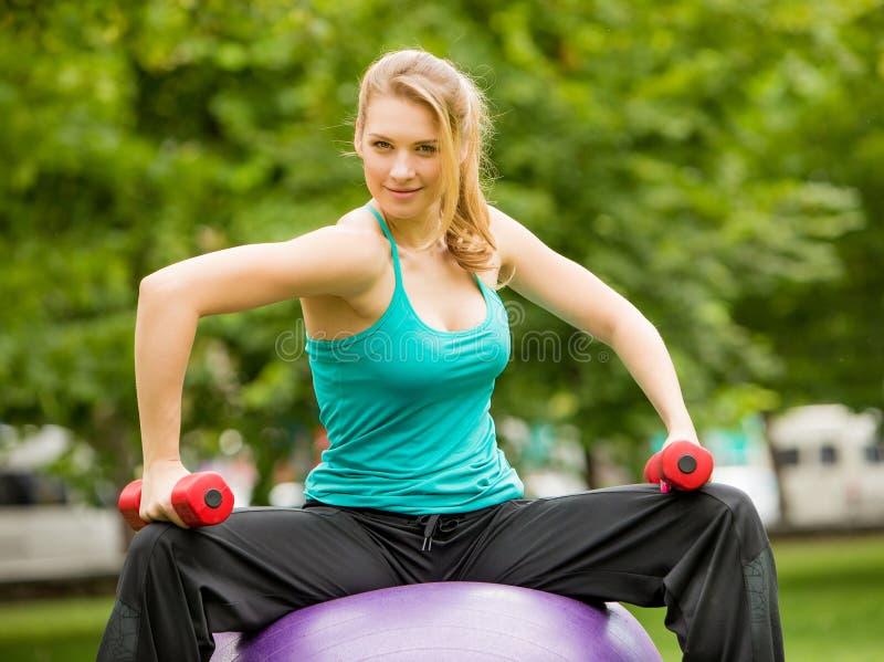 Ostenta o exercício da menina com pesos no parque fotos de stock royalty free