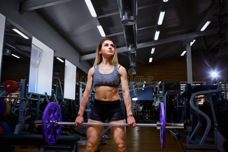 Ostente a menina com um barbell em seus braços no gym imagem de stock
