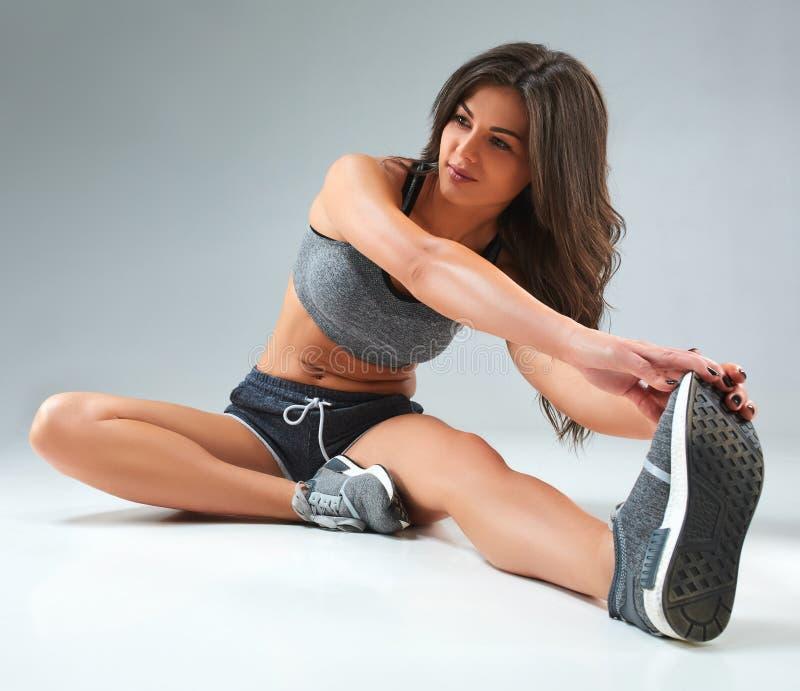 Ostente a mulher da aptidão, menina saudável nova que faz o esticão exercita no fundo cinzento imagem de stock