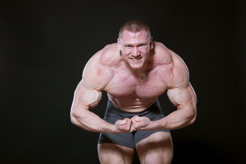 Ostente o atleta que o halterofilista mostra fora seus músculos fotografia de stock