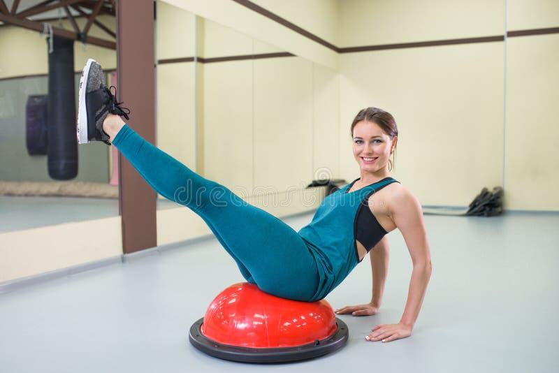 Ostente o exercício da mulher com uma bola dos pilates no gym, sorrindo e olhando a câmera fotografia de stock royalty free