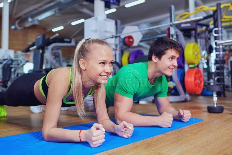 Ostente os pares que fazem a barra das flexões de braço no assoalho no gym imagem de stock