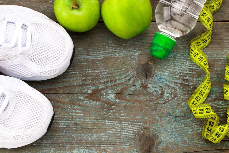 Ostente sapatas, maçãs, garrafa da água no fundo de madeira Concentrado imagens de stock royalty free