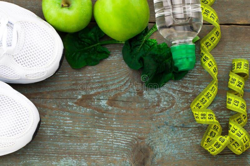 Ostente sapatas, maçãs, garrafa da água no fundo de madeira Concentrado fotografia de stock