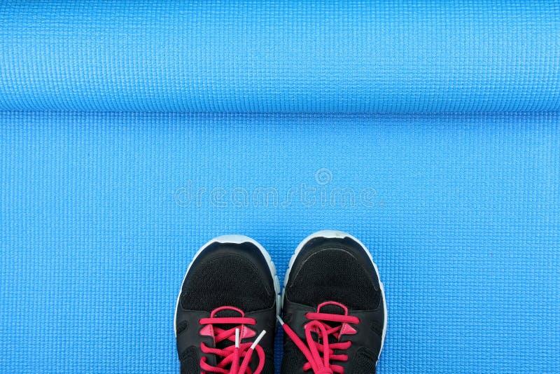 Ostente sapatas no fundo azul da esteira da ioga, acessórios da aptidão imagem de stock