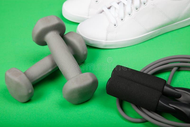 Ostente sapatas, pesos e corda de salto no fundo verde Aptidão, esporte e conceito saudável do estilo de vida fotos de stock