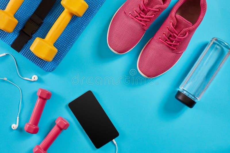 Ostente sapatas, pesos e telefone celular no fundo azul Vista superior Aptidão, esporte e conceito saudável do estilo de vida fotografia de stock