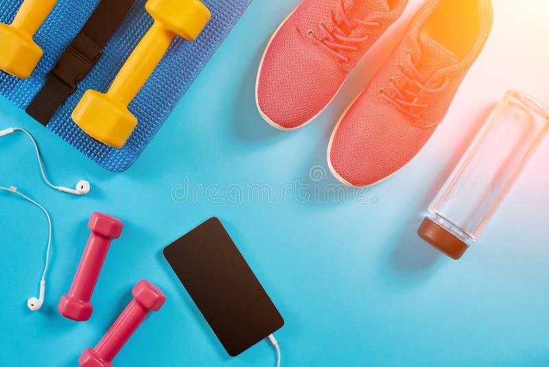 Ostente sapatas, pesos e telefone celular no fundo azul Vista superior Aptidão, esporte e conceito saudável do estilo de vida Sun imagens de stock