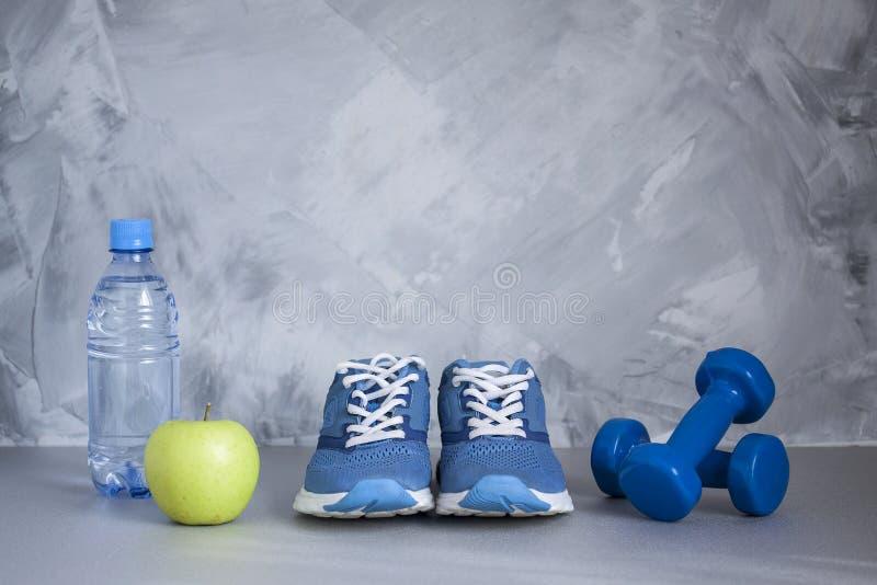 Ostente sapatas, pesos, maçã, garrafa da água no concreto cinzento fotografia de stock