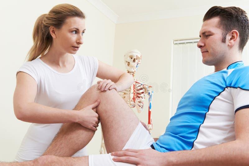Osteopat som behandlar den manliga patienten med sportskada royaltyfri foto