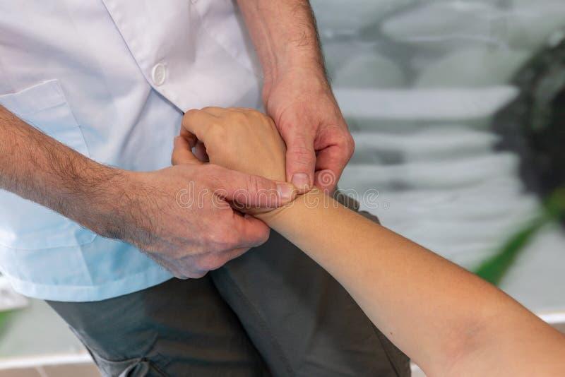 Osteopath ο θεράπων κάνει ένα λεμφατικό μασάζ στον καρπό στοκ εικόνα