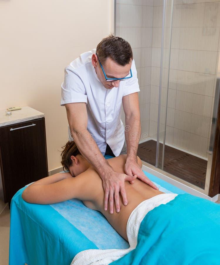 Osteopath ο θεράπων, κάνει το χειρισμό και τρίβει τον ασθενή με έναν τραυματισμό στοκ εικόνα