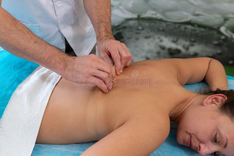 Osteopath τρίβει τον ασθενή σε την πίσω Σκλήρυνση του δέρματος στοκ εικόνες