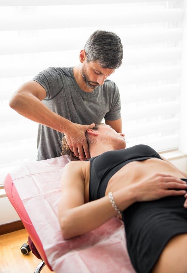 Osteopath executando terapia de confiança cervical foto de stock