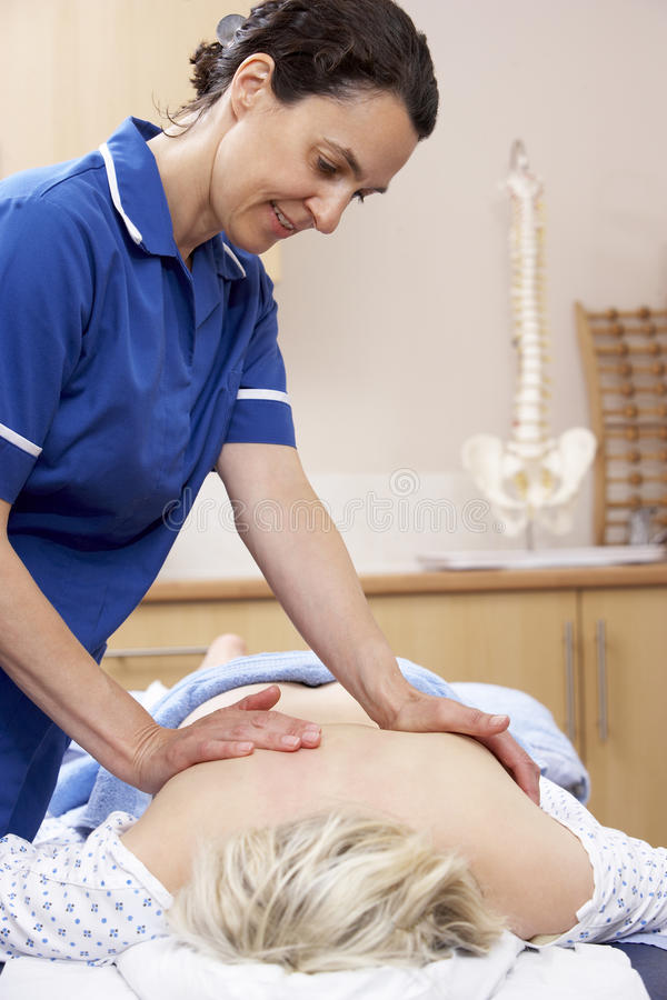 Osteopath treating female client. Osteopath concentrating whilst treating female client royalty free stock images