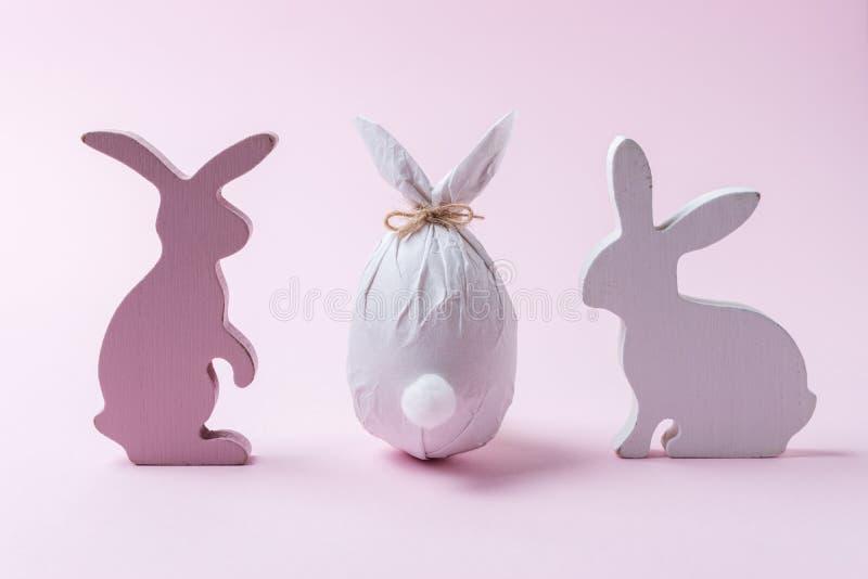 Osterei eingewickelt in einem Papier in Form eines Häschens mit Häschendekoration Minimales Ostern-Konzept stockfoto