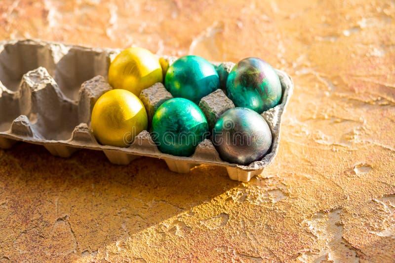 Ostereier auf gelber Tabelle Gelbe und rote Farben Ecke eines Behälters der bunten Eier Glückliches Ostern-Konzept stockbilder
