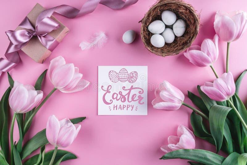 Ostereier in den Nest- und Tulpenblumen auf rosa Hintergrund mit Ostern-Karte stockfoto