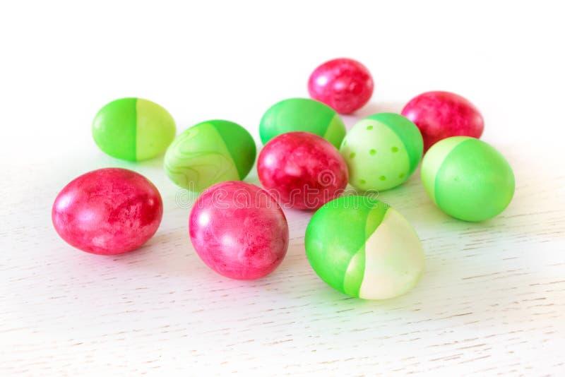 Ostereier gefärbt in den grünen und rosa Farben auf weißem hölzernem Vorsprung lizenzfreie stockfotos