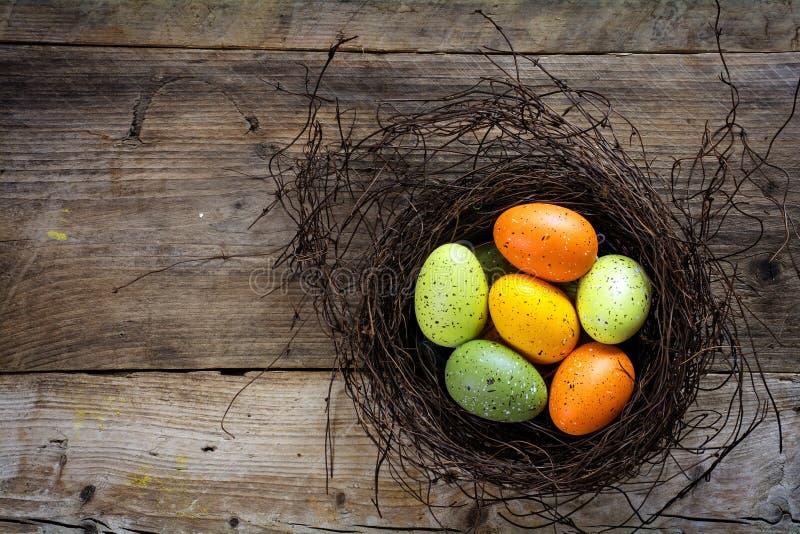 Ostereier grün und orange in einem Nest auf rustikalen hölzernen Planken w stockfotografie